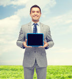 Happy businessman in suit showing tablet pc screen Stock Image
