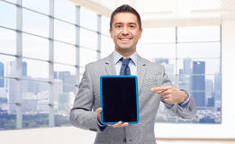 Happy businessman in suit showing tablet pc screen Royalty Free Stock Images