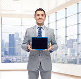 Happy businessman in suit showing tablet pc screen Stock Photography