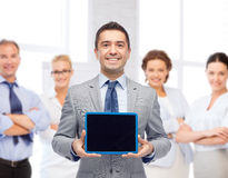 Happy businessman in suit showing tablet pc screen Royalty Free Stock Photos