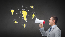 Happy businessman in suit speaking to megaphone. Business, people, idea and announcement concept - happy businessman in suit speaking to megaphone and light Stock Photo