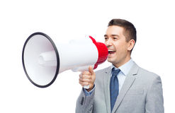 Happy businessman in suit speaking to megaphone Stock Photography
