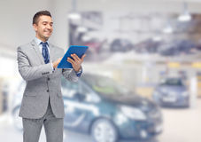 Happy businessman in suit with tablet pc. Business, people, car sale and technology concept - happy smiling businessman in suit holding tablet pc computer over Stock Photography