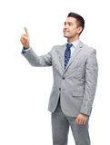 Happy businessman in suit touching something Stock Photo