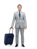 Happy businessman in suit with travel bag Stock Images