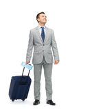 Happy businessman in suit with travel bag. Business trip, traveling, luggage and people concept - happy businessman in suit with travel bag and air ticket Royalty Free Stock Image