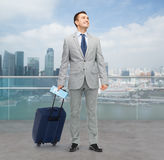 Happy businessman in suit with travel bag Royalty Free Stock Photography