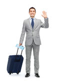 Happy businessman in suit with travel bag Royalty Free Stock Photos