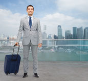 Happy businessman in suit with travel bag Royalty Free Stock Images