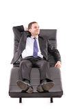 A happy businessman taking a rest on a sofa. Isolated on white royalty free stock image