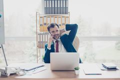 Happy businessman is talking on his phone, relaxed and smiling. royalty free stock photography