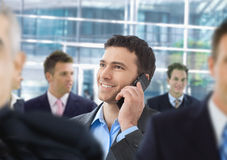 Happy businessman talking on mobile. Standing in crowd in office lobby Stock Image