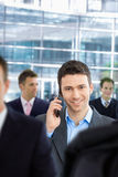 Happy businessman talking on mobile. Standing in crowd in office lobby Royalty Free Stock Image