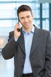 Happy businessman talking on mobile. Portrait of happy businessman talking on mobile in office lobby Stock Image