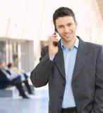 Happy businessman talking on mobile. Portrait of happy businessman talking on mobile in office hallway Stock Images
