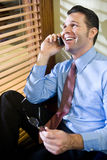Happy businessman talking on mobile phone. Happy male business executive talking on mobile phone in office Stock Photography