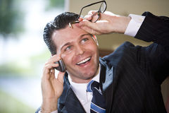 Happy businessman talking on mobile phone. Close up of happy businessman talking on mobile phone, looking up grinning Stock Images