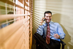 Happy businessman talking on mobile phone. Smiling male business executive talking on mobile phone in office Royalty Free Stock Photos