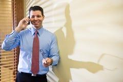 Happy businessman talking on mobile phone. Holding eyeglasses Royalty Free Stock Images