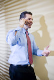 Happy businessman talking on mobile phone. Smiling male business executive talking on mobile phone in office Stock Image