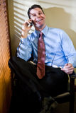 Happy businessman talking on mobile phone. Smiling male business executive talking on mobile phone in office Royalty Free Stock Photo