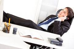 Happy businessman talking on mobile phone. Happy  business man sitting in office with feet on desk and talking on mobile phone Stock Photo