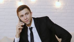 Portrait of a young man in a black suit talking on the phone. Happy businessman talking mobile phone in home workplace. Business conversation with perfect result stock video