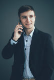 Happy businessman talking on the mobile phone over black background. Looking away Royalty Free Stock Photography
