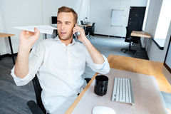 Happy businessman talking on mobile phone and throwing paper plane Stock Photo