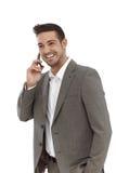 Happy businessman talking on mobile. Happy young businessman talking on mobile phone over white background Stock Photos