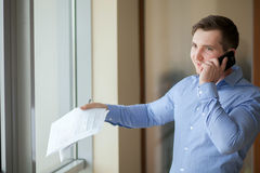 Happy businessman talking on the phone at office Royalty Free Stock Image