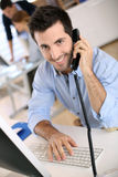 Happy businessman talking on phone in office Stock Photography