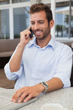 Happy businessman talking on phone using his laptop. In patio of restaurant Stock Images