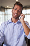 Happy businessman talking on the phone after work. In a bar Stock Photography