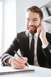 Happy businessman talking by phone and writing notes. Image of happy businessman sitting in office while talking by phone and writing notes Stock Photo