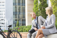 Happy businessman talking to female colleague in city Stock Photos
