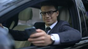 Happy businessman texting with girlfriend and smiling while sitting in car. Stock footage stock video footage