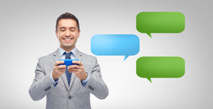 Happy businessman texting message on smartphone Stock Photo