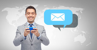 Happy businessman texting message on smartphone Royalty Free Stock Photos