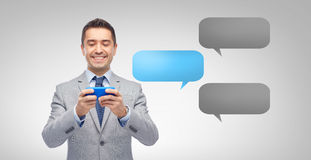 Happy businessman texting message on smartphone Stock Image