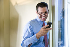Happy businessman texting on mobile phone Royalty Free Stock Image
