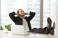 Happy businessman thinking about good perspectives. Smiling businessman looking up, sitting with legs on desk and hands behind head. Successful entrepreneur Stock Images