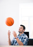Happy businessman throwing ball in office Stock Photos