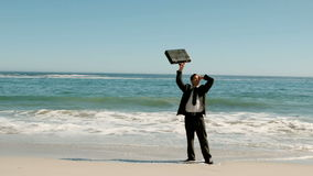 Happy businessman throwing his suitcase on the beach Royalty Free Stock Images