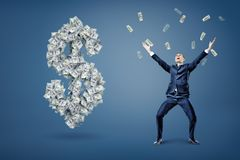 A happy businessman throws and catches money near a large dollar sign made of banknotes. stock illustration