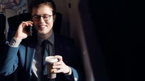Happy businessman in the train talking on the smart phone and drinking coffee. Young businessman traveling by the train speaks by smartphone and drinking coffee stock video