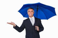 Happy businessman under umbrella with hand out Stock Image