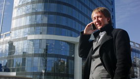 Happy businessman using cell phone outside office stock video footage