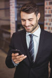 Happy businessman using cellphone in office Stock Photo
