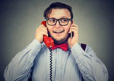 Happy businessman using cellphone and retro style telephone at once. Happy business man using cellphone and retro style telephone at once stock photo